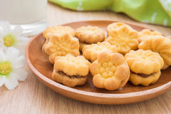 Flower shape biscuits with jam filling on wooden plate Stock Image