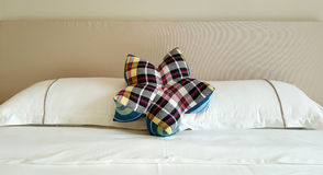 Flower shape pliad pillow on white bed sheet Royalty Free Stock Photography