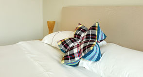 Flower shape pliad pillow on white bed sheet Stock Image