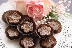 Flower shaped Brownies. On glassine brown cups served on a lace doily and decorated with a white rose with pink borders and gypsophilas stock image