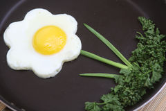 Flower shaped fried egg with greenery Royalty Free Stock Images