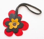 Flower shaped handmade leather pendant. On white board royalty free stock image