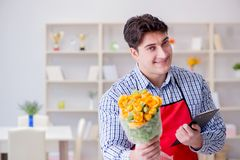 The flower shop assistant offering a bunch of flowers. Flower shop assistant offering a bunch of flowers Royalty Free Stock Images