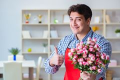 The flower shop assistant offering a bunch of flowers. Flower shop assistant offering a bunch of flowers Royalty Free Stock Image