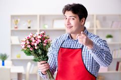 The flower shop assistant offering a bunch of flowers. Flower shop assistant offering a bunch of flowers Stock Photos