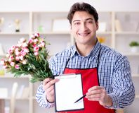 Flower shop assistant offering a bunch of flowers royalty free stock photos
