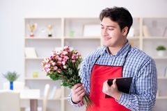 The flower shop assistant offering a bunch of flowers. Flower shop assistant offering a bunch of flowers Royalty Free Stock Photography