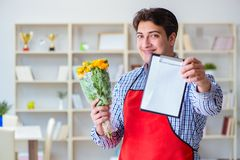 The flower shop assistant offering a bunch of flowers. Flower shop assistant offering a bunch of flowers Royalty Free Stock Photo