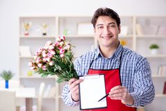 The flower shop assistant offering a bunch of flowers. Flower shop assistant offering a bunch of flowers Stock Photography