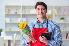 The flower shop assistant offering a bunch of flowers. Flower shop assistant offering a bunch of flowers Stock Photo