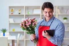 The flower shop assistant offering a bunch of flowers. Flower shop assistant offering a bunch of flowers Stock Image