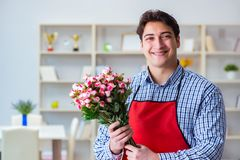 The flower shop assistant offering a bunch of flowers. Flower shop assistant offering a bunch of flowers Stock Images