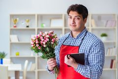 The flower shop assistant offering a bunch of flowers. Flower shop assistant offering a bunch of flowers Royalty Free Stock Photos