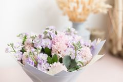 Flower shop concept. Close-up beautiful lovely bouquet of mixed flowers on wooden table. Wallpaper. Beautiful luxury bouquet of mixed flowers in woman hand. the Stock Photos