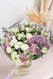 Flower shop concept. Close-up beautiful luxury bouquet of mixed flowers on wooden table. Wallpaper. Beautiful luxury bouquet of mixed flowers in woman hand. the Stock Image
