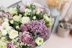 Flower shop concept. Close-up beautiful luxury bouquet of mixed flowers on wooden table. Wallpaper. Beautiful luxury bouquet of mixed flowers in woman hand. the Stock Photo