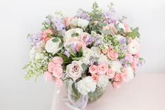 Flower shop concept. Close-up beautiful luxury bouquet of mixed flowers on wooden table. Wallpaper. Beautiful luxury bouquet of mixed flowers in woman hand. the stock images