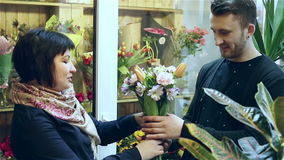 In the flower shop. Florist is giving the finished bouquet of flowers to the hands of the customer. stock video