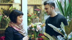 In the flower shop. Florist is holding a bouquet of flowers and telling the client from which flowers it is composed. stock video