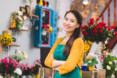 Flower shop owner. Confident Vietnamese flower shop owner smiling and looking at the camera Royalty Free Stock Photo