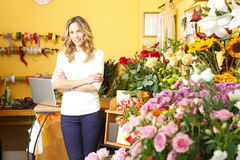 Flower shop owner. Small business. Portrait of friendly small flower shop owner standing in front of counter. Looking at camera and smiling stock photography