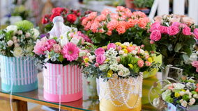 Flower shop, on the show-window, there are a lot of bouquets of flowers from pion-shaped roses, floral stylish. Compositions in colorful boxes with different stock video footage