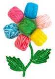 Flower from skeins of thread and crocheted petals. Composition in the form of a flower. Flower bud consists of multi-colored skeins of yarn. Leaves and stem are Royalty Free Stock Photos