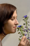 Flower smelling. Woman smelling the flower outdoor Royalty Free Stock Image