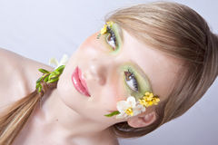 Flower spring face art portrait. Studio white background portrait of a beautyful blond girl with face art and spring flowers in hair and on face Stock Photos
