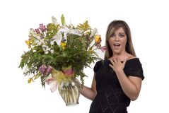 Flower Surprise. Expressive blond model in studio holding fresh bouquet of floers Royalty Free Stock Photos