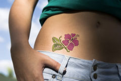 Flower tattoo. On the skin of a young stock photos
