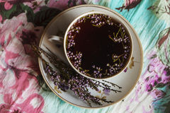 Flower tea. Cup with floral tea and flowers of heather Royalty Free Stock Photo
