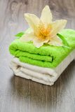Flower on towels on wooden background Stock Images