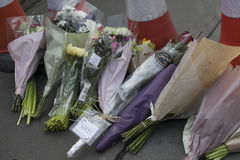 Flower tributes are left on the pavement on the edge of a police Royalty Free Stock Photos