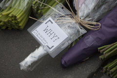 Flower tributes are left on the pavement on the edge of a police Stock Image