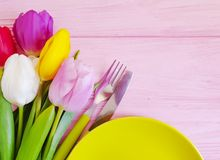 Flower tulip, a plate on a pink wooden romantic background, birthday. Flower tulip, a plate on a pink wooden background birthday romantic royalty free stock images
