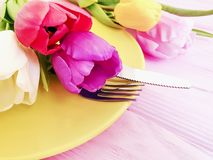 Flower tulip blooming , a plate decorative dinner on a pink wooden romantic background, birthday. Flower tulip, a plate on a pink wooden background romantic stock photography