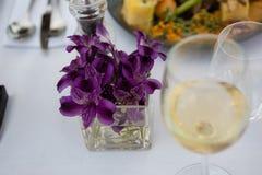Flower vase by white wine on table in restaurant Stock Photo