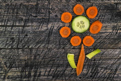 Flower vegetable early board wooden carrots cucumber leek Royalty Free Stock Images