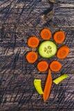 Flower vegetable early board wooden carrots cucumber leek Royalty Free Stock Photos