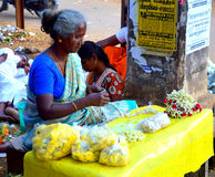 Flower vendor Alongside the Road. Poor street woman selling flower for a living Alongside a Road in India stock photography