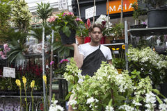 Flower vendor in the Columbia Road Flower Markets spins his sales patter while holding a single flower. LONDON, ENGLAND - JULY 14: Flower vendor in the Columbia stock image
