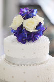 Flower Wedding Cake topper. Three tier wedding cake with blue and white flower topper. White cake with jewels stock image