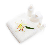 Flower white Lily lying on a towel and bottles.  Royalty Free Stock Photo
