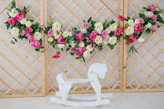 A flower wreath standing near the wooden horse Royalty Free Stock Photo