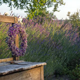 Flower wreath on a wooden bench. Lavender flower wreath on a wooden old bench in a summer garden Stock Photos