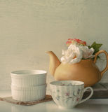 Flower in a yellow tea pot and vintage cup of coffee on wooden b Royalty Free Stock Images