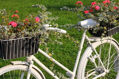 Flowerbad with flowers made from bike. Original flowebad made from old bike painted in white Stock Photography