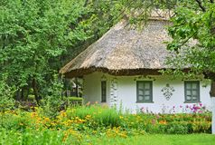 Flowerbed and ancient hut Royalty Free Stock Photos