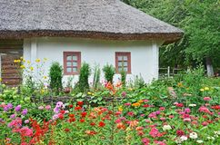 Flowerbed and ancient hut Stock Images
